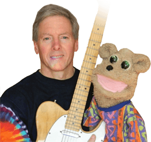 Kim Webster sits with his electric guitar and a puppet called Ted Bear.